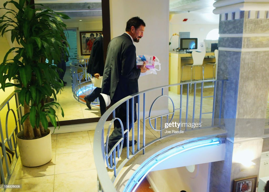 John McAfee walks to his room at the Beacon Hotel where he is staying after arriving last night from Guatemala on December 13, 2012 in Miami Beach, Florida. McAfee is a 'person of interest' in the fatal shooting of his neighbor in Belize and turned up in Guatemala after a month on the run in Belize.