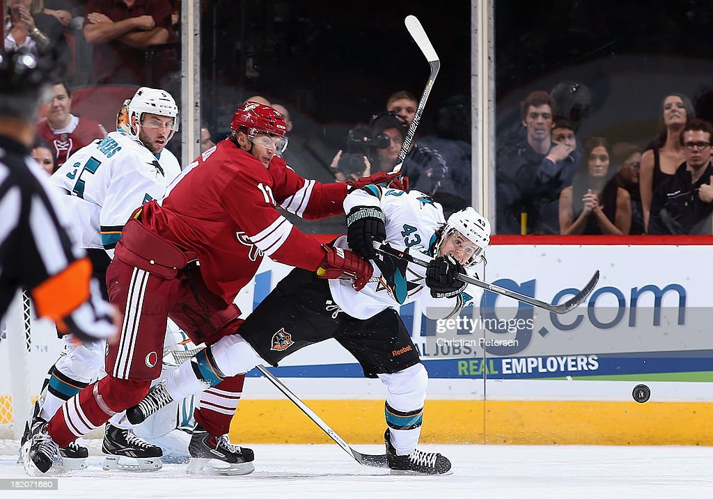 John McCarthy #43 of the San Jose Sharks clears the puck pressured by Martin Hanzal #11 of the Phoenix Coyotes during the preseason NHL game at Jobing.com Arena on September 27, 2013 in Glendale, Arizona.