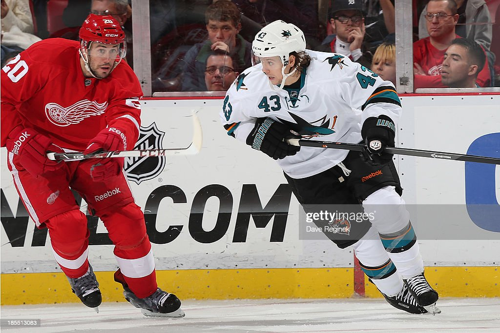 John McCarthy #43 of the San Jose Sharks tries to skate past Drew Miller #20 of the Detroit Red Wings during an NHL game at Joe Louis Arena on October 21, 2013 in Detroit, Michigan.