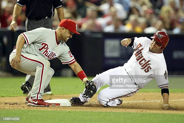 John McDonald of the Arizona Diamondbacks slides in safely to third base ahead of the tag from infielder Placido Polanco of the Philadelphia Phillies...