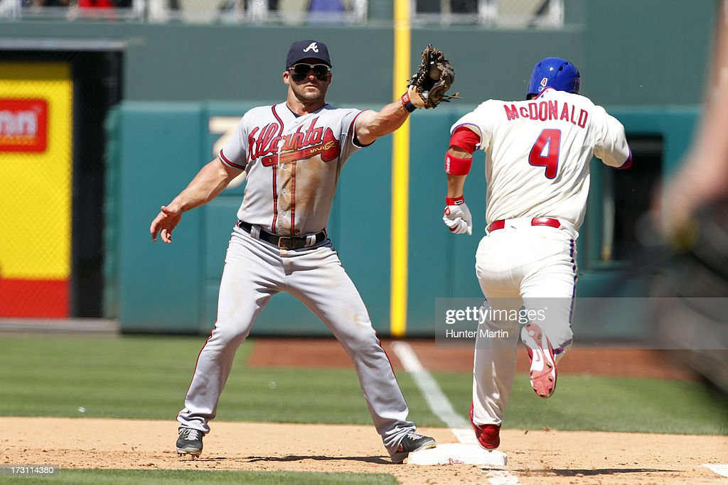 <a gi-track='captionPersonalityLinkClicked' href=/galleries/search?phrase=John+McDonald+-+Baseball+Player&family=editorial&specificpeople=215395 ng-click='$event.stopPropagation()'>John McDonald</a> #4 of the Philadelphia Phillies is thrown out at first as <a gi-track='captionPersonalityLinkClicked' href=/galleries/search?phrase=Dan+Uggla&family=editorial&specificpeople=542208 ng-click='$event.stopPropagation()'>Dan Uggla</a> #26 of the Atlanta Braves takes the throw during a game at Citizens Bank Park on July 7, 2013 in Philadelphia, Pennsylvania. The Phillies won 7-3.
