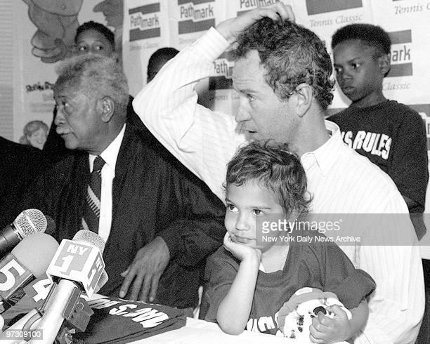 John McEnroe at Press Conference for tennis game to honor Arthur Ashe Little girl on McEnroe's lap is 3yearold Christine Adler
