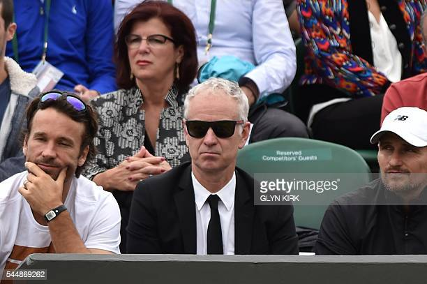 John McEnroe coach of Canada's Milos Raonic watches Raonic play against Belgium's David Goffin during their men's singles fourth round match on the...