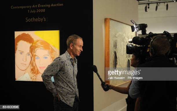 John McEnroe is interviewed alongside Andy Warhol's portrait of John McEnroe and Tatum O'Neal at Sotherby's in central London