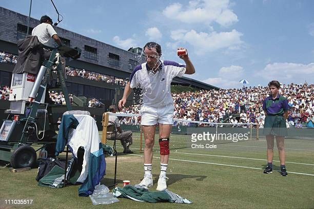 John McEnroe of the United States cools down by splashing water onto his face during his Men's Singles match against Andre Olhovskiy at the Wimbledon...