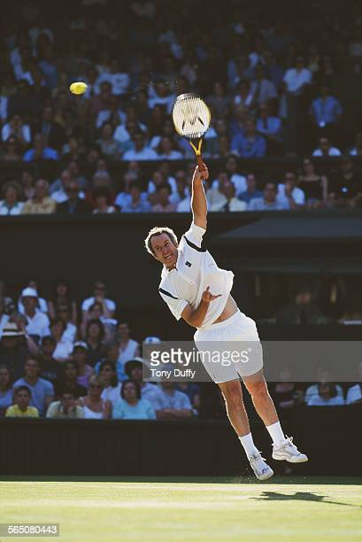 John McEnroe of the United States serves during his Mixed Doubles match with Steffi Graf at the Wimbledon Lawn Tennis Championship on 2 July 1999 at...