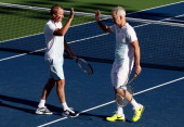 John McEnroe of the United States taps hands with his partner Patrick McEnroe of the United States during their men's champions doubles match against...