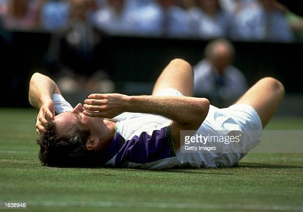 John McEnroe of the USA collapses on the floor in disapointment against Andre Agassi of the USA during Wimbledon in London England Mandatory Credit...