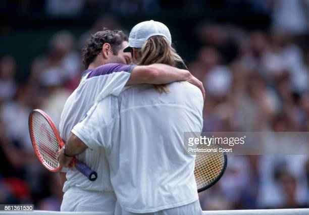 John McEnroe of the USA embraces Andre Agassi of the USA after McEnroe loses their SemiFinal match during the Wimbledon Lawn Tennis Championships at...