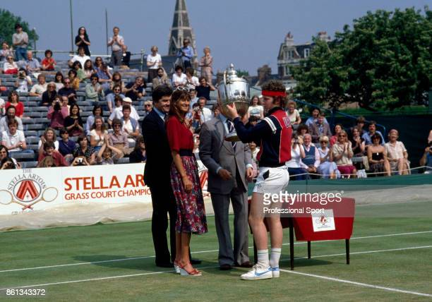 John McEnroe of the USA lifts the trophy after defeating Kim Warwick of Australia to win the Stella Artois Championships at the Queen's Club in...