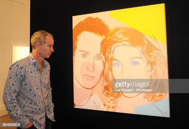 John McEnroe poses alongside Andy Warhol's portrait of John McEnroe and Tatum O'Neal at Sotherby's in central London