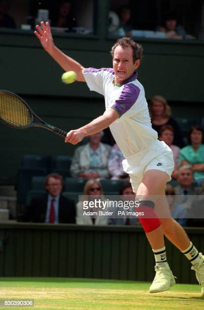 John McEnroe returns a shot to Andre Agassi during the early stages of their rain delayed semi final on Centre Court