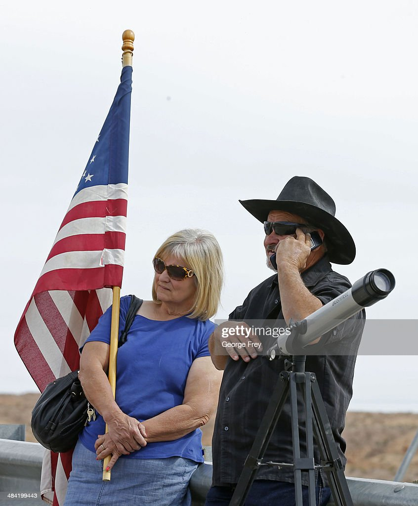 John McLaughlin (R) and his wife Cindy (L) talks on the phone at a protest area along U.S. 170 April 11, 2014 west of Mesquite, Nevada. Bureau of Land Management officials are rounding up Cliven Bundy's cattle, he has been locked in a dispute with the BLM for a couple of decades over grazing rights. (Photo by George Frey/Getty Images