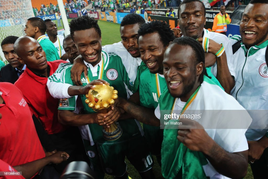 John Mikel Obi and <a gi-track='captionPersonalityLinkClicked' href=/galleries/search?phrase=Victor+Moses&family=editorial&specificpeople=2649383 ng-click='$event.stopPropagation()'>Victor Moses</a> lead celebrations with team mates with the trophy after winning the 2013 Africa Cup of Nations Final match between Nigeria and Burkina at FNB Stadium on February 10, 2013 in Johannesburg, South Africa.