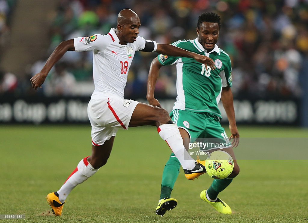 John Mikel Obi of Nigeria is tackled by Charles Kabore during the 2013 Africa Cup of Nations Final match between Nigeria and Burkina at FNB Stadium on February 10, 2013 in Johannesburg, South Africa.