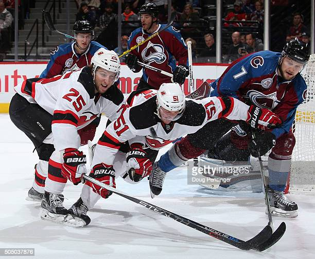 John Mitchell of the Colorado Avalanche clears the puck away from Stefan Matteau and Sergey Kalinin of the New Jersey Devils at Pepsi Center on...