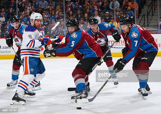 John Mitchell of the Colorado Avalanche controls the puck as Nate Guenin of the Colorado Avalanche defends against Matt Fraser of the Edmonton Oilers...