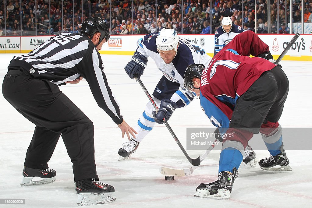 John Mitchell #7 of the Colorado Avalanche faces off against <a gi-track='captionPersonalityLinkClicked' href=/galleries/search?phrase=Olli+Jokinen&family=editorial&specificpeople=202946 ng-click='$event.stopPropagation()'>Olli Jokinen</a> #12 of the Winnipeg Jets at the Pepsi Center on October 27, 2013 in Denver, Colorado.