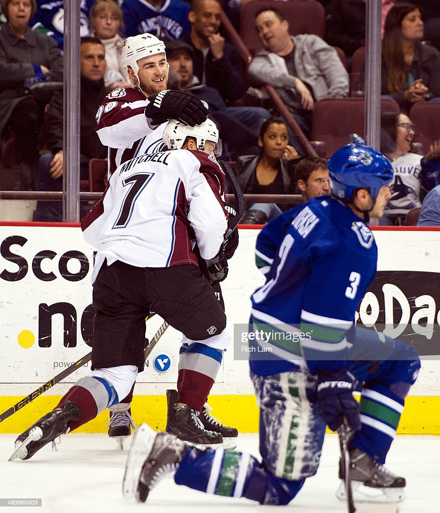 John Mitchell #7 of the Colorado Avalanche is congratulated by teammate <a gi-track='captionPersonalityLinkClicked' href=/galleries/search?phrase=Ryan+O%27Reilly&family=editorial&specificpeople=4754037 ng-click='$event.stopPropagation()'>Ryan O'Reilly</a> #90 after scoring an empty net goal while Kevin Bieksa #3 of the Vancouver Canucks gets up from the ice during the third period in NHL action on April 10, 2014 at Rogers Arena in Vancouver, British Columbia, Canada.