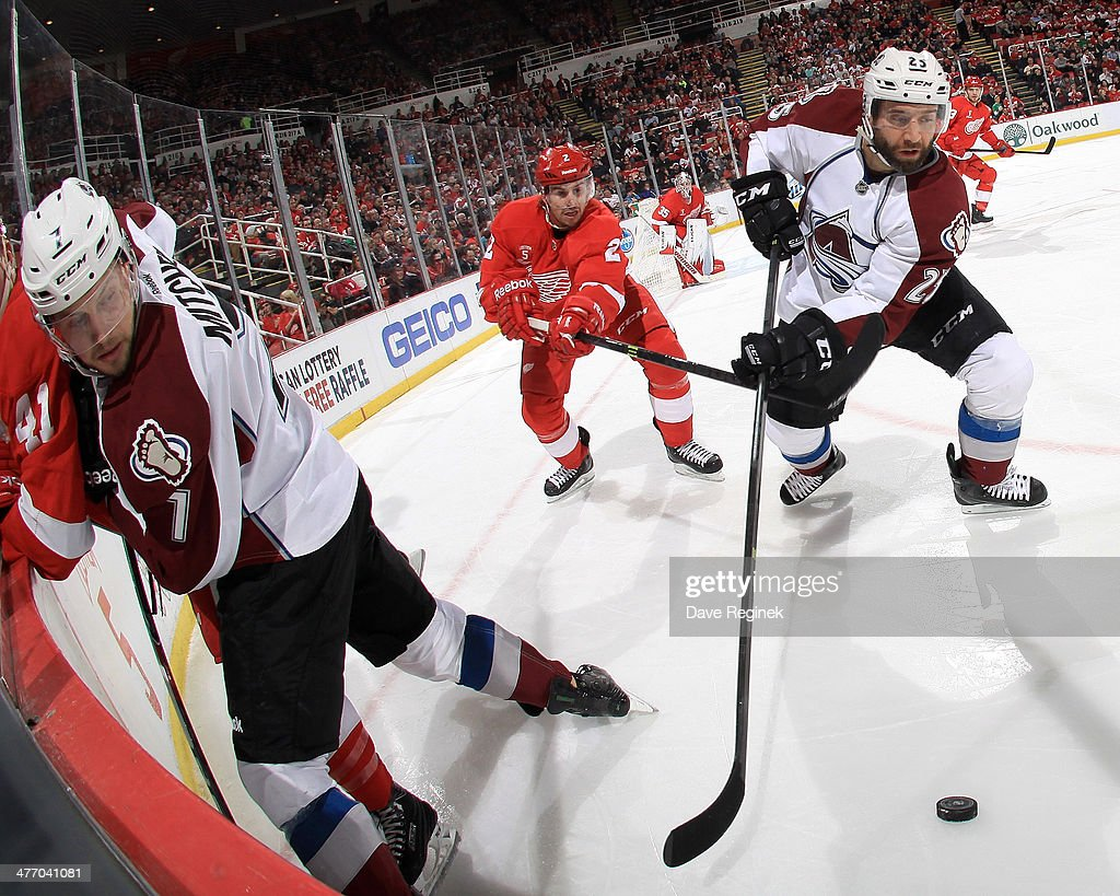 John Mitchell #7 of the Colorado Avalanche pins Luke Glendening #41 of the Detroit Red Wings along the boards as Avalanche teammate <a gi-track='captionPersonalityLinkClicked' href=/galleries/search?phrase=Maxime+Talbot&family=editorial&specificpeople=2078922 ng-click='$event.stopPropagation()'>Maxime Talbot</a> #25 scoops up the puck against Wings defenseman Brendan Smith #2 during an NHL game on March 6, 2014 at Joe Louis Arena in Detroit, Michigan.