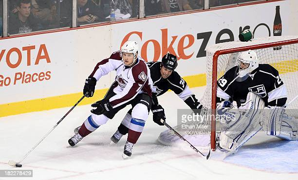 John Mitchell of the Colorado Avalanche skates around the net as Willie Mitchell and goalie Mathieu Garon of the Los Angeles Kings defend during...