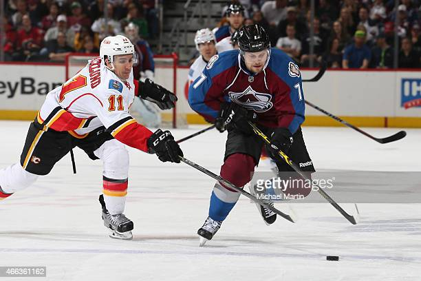 John Mitchell of the Colorado Avalanche skates with the puck as he is challenged by Mikael Backlund of the Calgary Flames at the Pepsi Center on...
