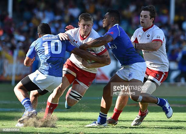 John Moonlight of Canada is tackled by Samoa Toloa and Tomasi Alosio of Samoa in the Bowl final at the Sydney Sevens rugby union tournament in Sydney...