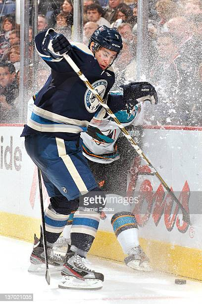 John Moore of the Columbus Blue Jackets checks Logan Couture of the San Jose Sharks into the boards while battling for control of the puck during the...
