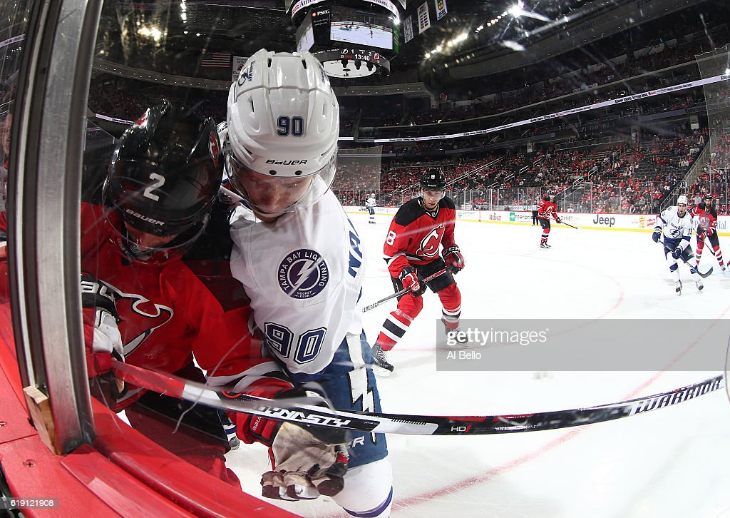 John Moore #2 of the New Jersey Devils battles for the puck against Vladislav Namestnikov #90 of the Tampa Bay Lightning during their game at the Prudential Center on October 29, 2016 in Newark, New Jersey.
