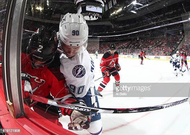 John Moore of the New Jersey Devils battles for the puck against Vladislav Namestnikov of the Tampa Bay Lightning during their game at the Prudential...