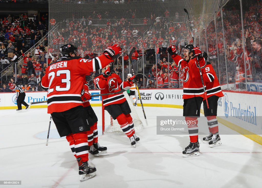 John Moore #2 of the New Jersey Devils (R) celebrates his game winning overtime goal at 59 seconds against the Philadelphia Flyers at the Prudential Center on April 4, 2017 in Newark, New Jersey.