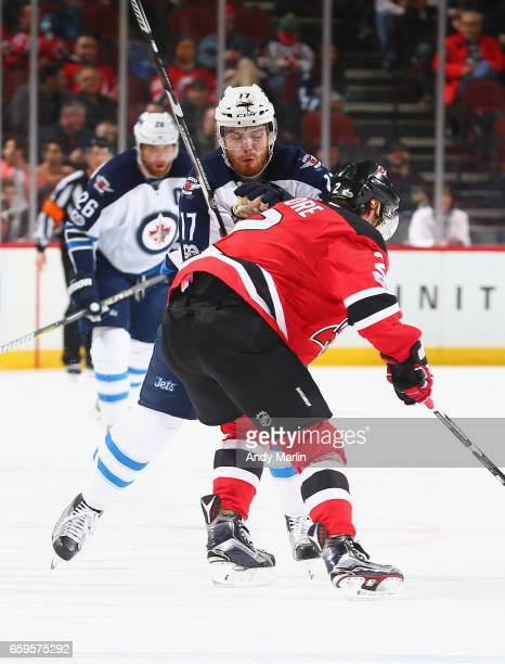 John Moore of the New Jersey Devils checks Adam Lowry of the Winnipeg Jets during the game at Prudential Center on March 28 2017 in Newark New Jersey