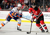 John Moore of the New Jersey Devils controls the puck in front of Brock Nelson of the New York Islanders during the first period at the Prudential...