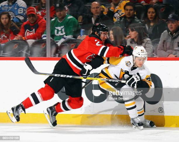 John Moore of the New Jersey Devils hits Josh Archibald of the Pittsburgh Penguins during the first period at the Prudential Center on April 6 2017...
