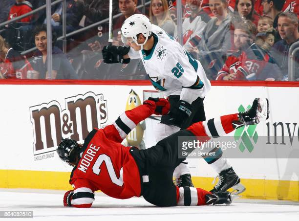 John Moore of the New Jersey Devils is checked by Timo Meier of the San Jose Sharks during the second period at the Prudential Center on October 20...