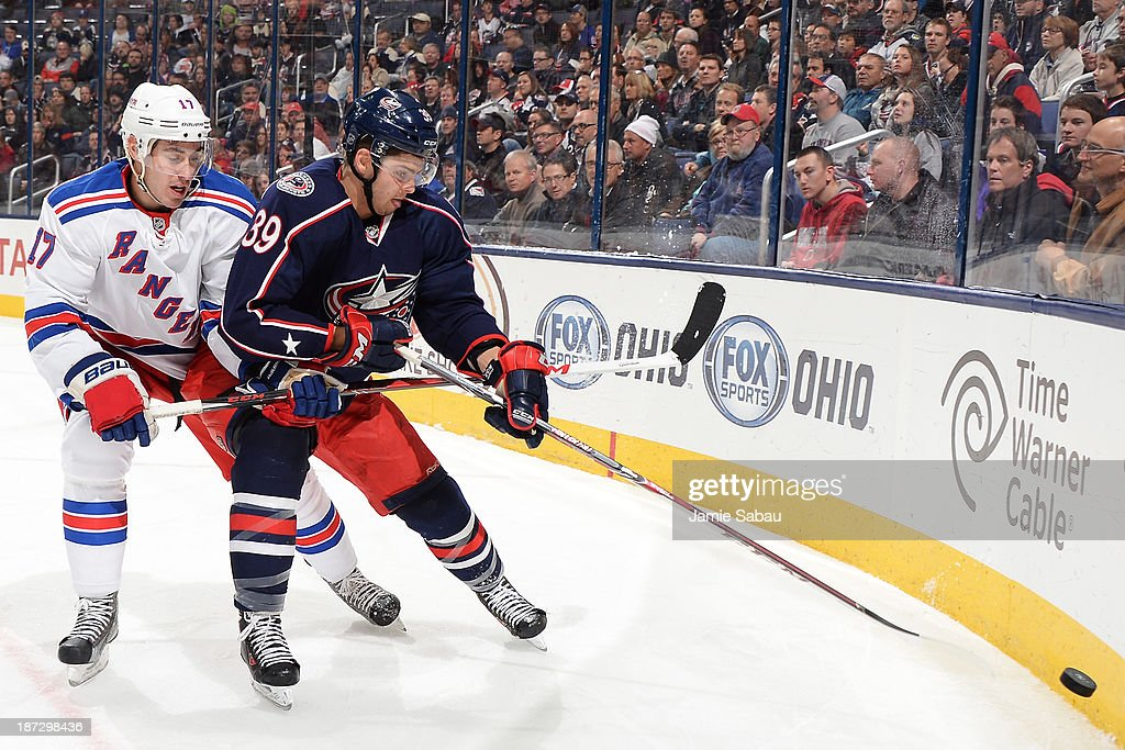 John Moore #17 of the New York Rangers and Michael Chaput #39 of the Columbus Blue Jackets battle for a loose puck during the third period on November 7, 2013 at Nationwide Arena in Columbus, Ohio. New York defeated Columbus 4-2.