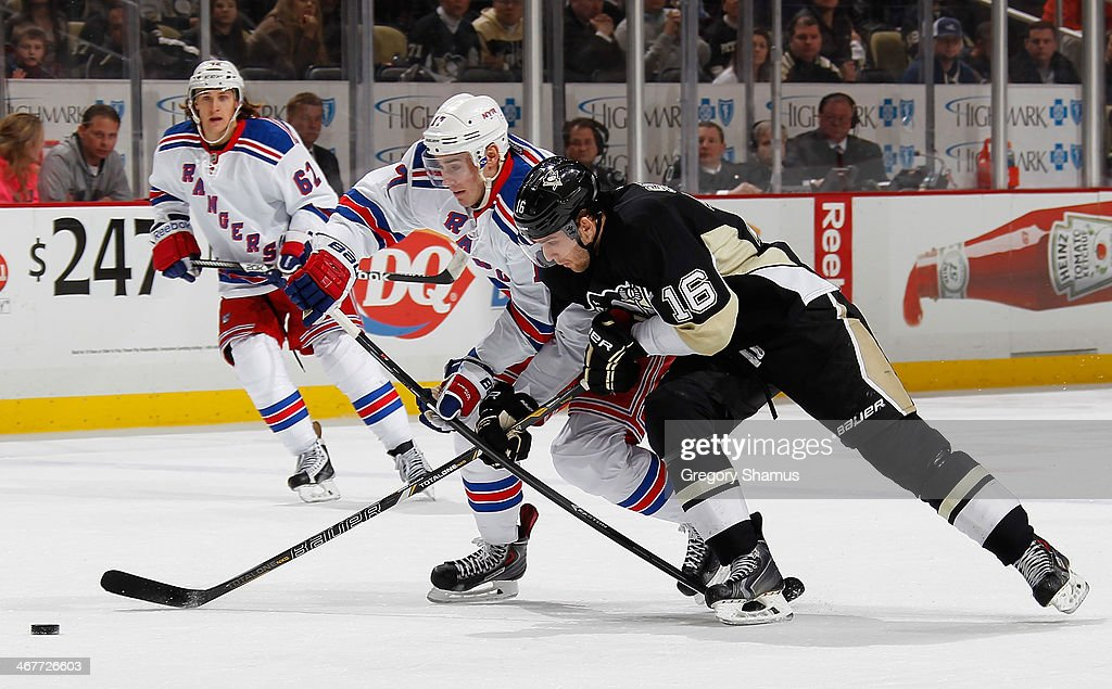 John Moore #17 of the New York Rangers battles for the puck against <a gi-track='captionPersonalityLinkClicked' href=/galleries/search?phrase=Brandon+Sutter&family=editorial&specificpeople=2086411 ng-click='$event.stopPropagation()'>Brandon Sutter</a> #16 of the Pittsburgh Penguins on February 7, 2014 at Consol Energy Center in Pittsburgh, Pennsylvania.