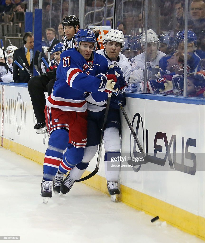 John Moore #17 of the New York Rangers rubs Matt Carle #25 of the Tampa Bay Lightning out into the boards during the first period at Madison Square Garden on January 14, 2014 in New York City.