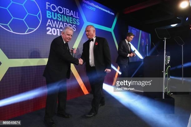 John Motson receives the Global Football Ambassador award from Philip Bernie Head of TV Sport at BBC during the Football Business Awards evening at...