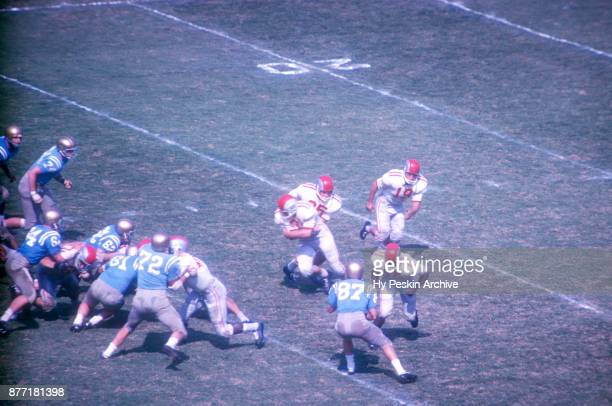 John Mummey of the Ohio State Buckeyes fakes the handoff to David Francis as Paul Warfield blocks Dave Gibbs of the UCLA Bruins during an NCAA game...