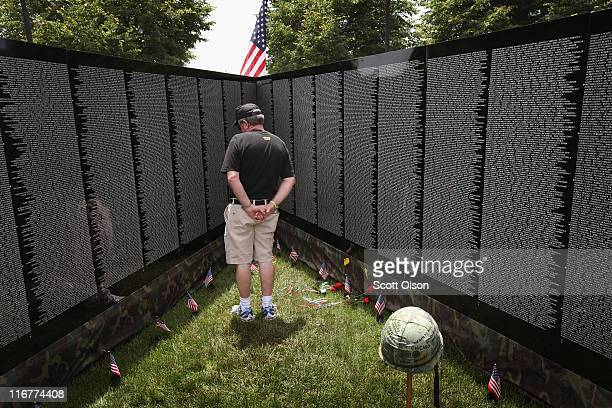 John O'Connor who served in Vietnam with the Army from 1967 to 1968 reads names inscribed on the Moving Wall display a halfsize replica of the...