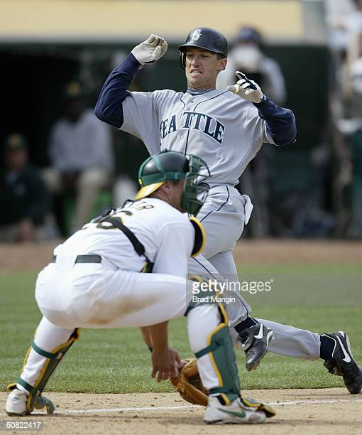 John Olerud of the Seattle Mariners slides into home as catcher Damian Miller of the Oakland Athletics looks to tag him out during the game at...