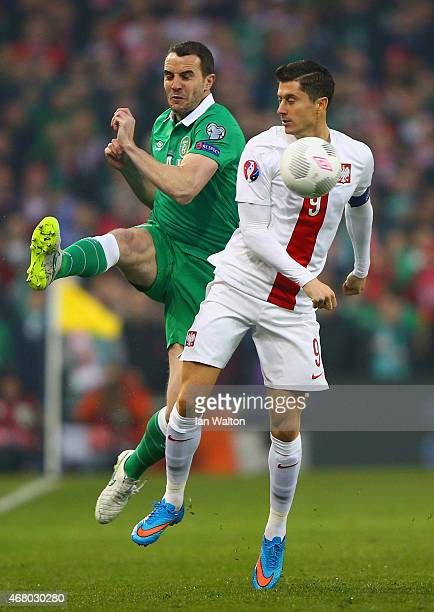 John O'Shea of Republic of Ireland and Robert Lewandowski of Poland compete for the ball during the EURO 2016 Qualifier match between Republic of...