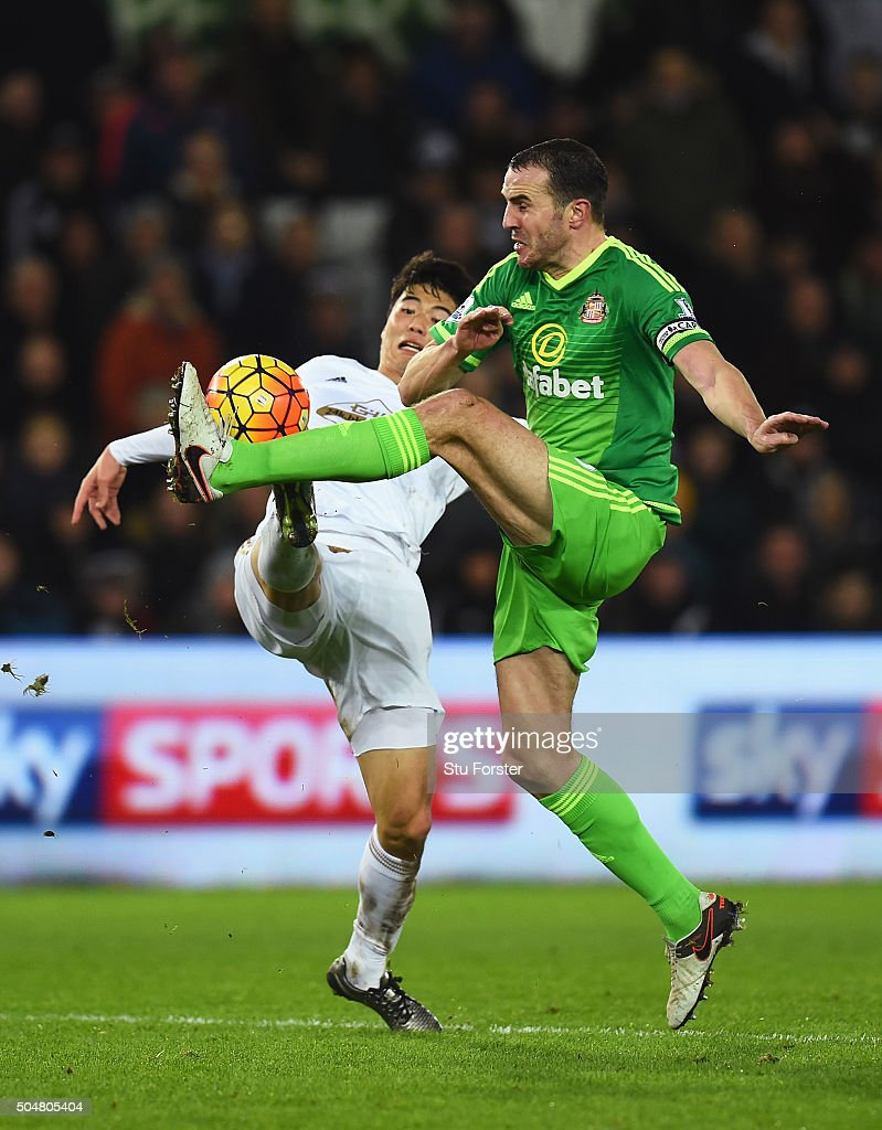 John O'Shea of Sunderland and Ki Sung-Yeung of Swansea City compete for the ball during the Barclays Premier League match between Swansea City and Sunderland at the Liberty Stadium on January 13, 2016 in Swansea, Wales.