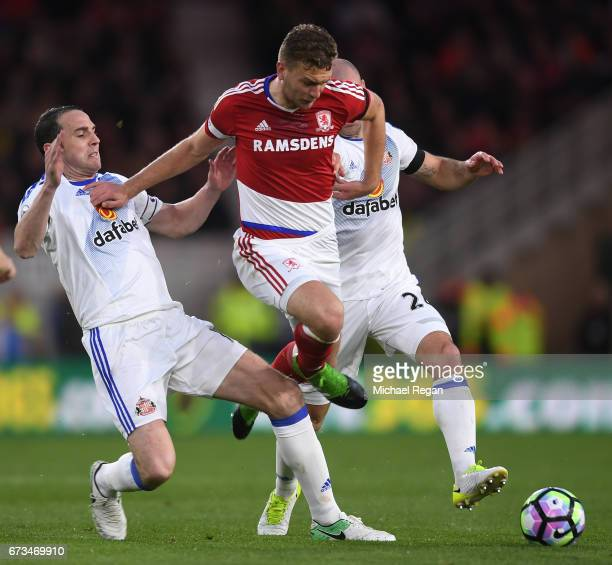 John O'Shea of Sunderland and Lee Cattermole of Sunderland tackle Ben Gibson of Middlesbrough during the Premier League match between Middlesbrough...