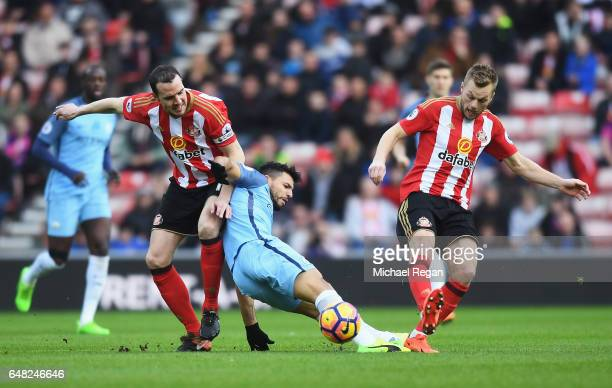 John O'Shea of Sunderland and Sergio Aguero of Manchester City battle for possession during the Premier League match between Sunderland and...