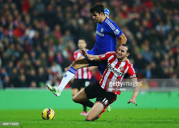 John O'Shea of Sunderland challenges Diego Costa of Chelsea during the Barclays Premier League match between Sunderland and Chelsea at Stadium of...
