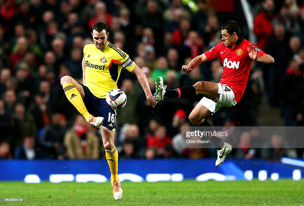 John O'Shea of Sunderland controls the ball under pressure from Javier Hernandez of Manchester United during the Capital One Cup semi final, second leg match between Manchester United and Sunderland at Old Trafford on January 22, 2014 in Manchester, England.