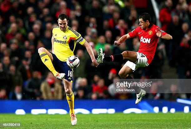 John O'Shea of Sunderland controls the ball under pressure from Javier Hernandez of Manchester United during the Capital One Cup semi final second...