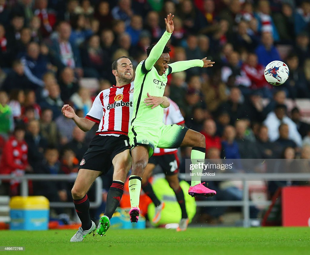 John O'Shea of Sunderland holds onto Raheem Sterling of Manchester City during the Capital One Cup third round match between Sunderland and Manchester City at Stadium of Light on September 22, 2015 in Sunderland, England.